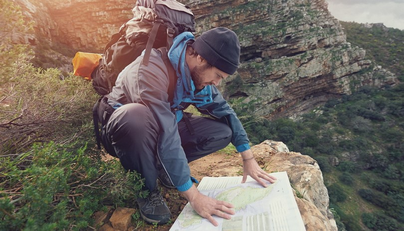 Lost hiker with backpack checks map to find directions in wilder