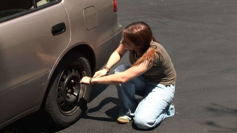 Woman trying to change a tire