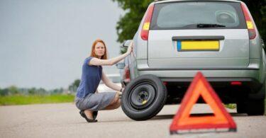 Driver fixing flat tire